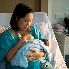 A mother breastfeeding in a hospital bed